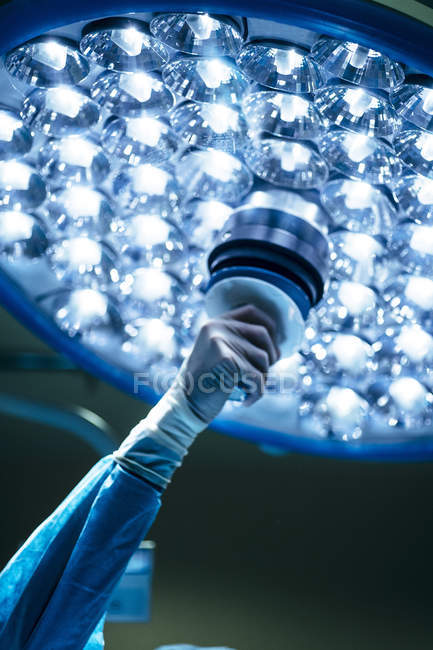 Crop shot of hand in glove setting adequate position of bright burning lamp in operating room. — Stock Photo
