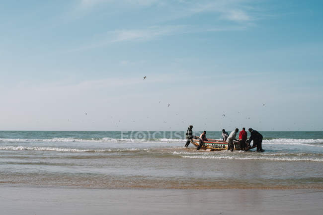 Yoff, Senegal- December 6, 2017: Distant view to group of people  at beach pushing boat to ocean — Stock Photo