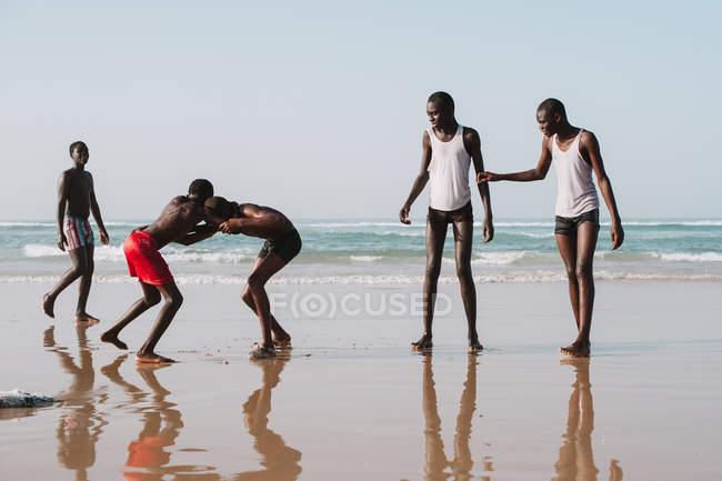 Yoff, Senegal - 6 de dezembro de 2017: Grupo de jovens africanos se divertindo na praia do oceano e lutando alegremente . — Fotografia de Stock