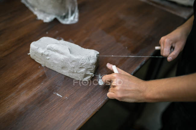 Crop female hands cutting piece of clay with string on wooden table — Stock Photo