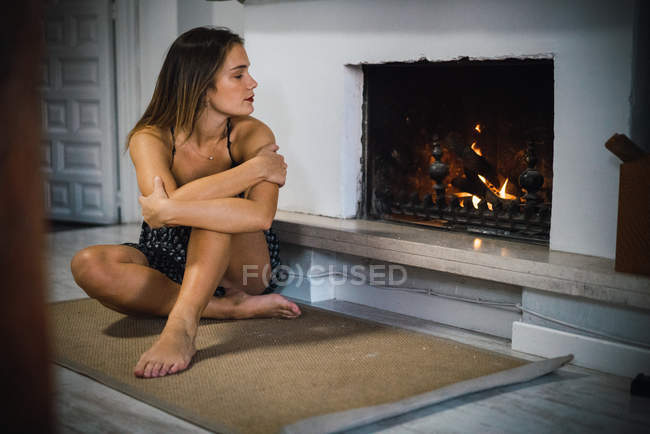 Portrait of bare feet woman sitting near fireplace and looking at flames — Stock Photo