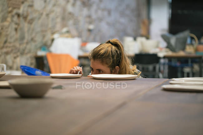Concentrated potter working on crockery creation in workshop — Stock Photo