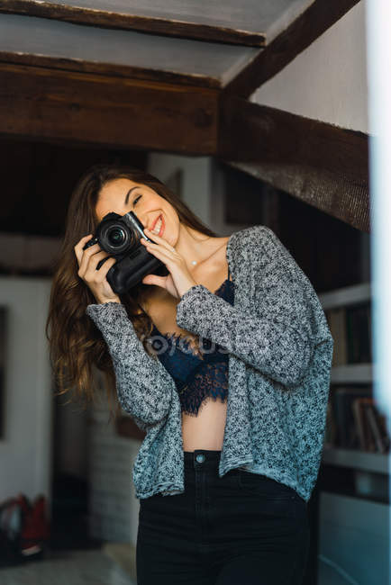 Portrait of cheerful brunette in casual posing with photo camera and taking photo. — Stock Photo