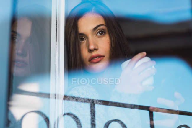 Brunette girl with cup of coffee seen through window — Stock Photo