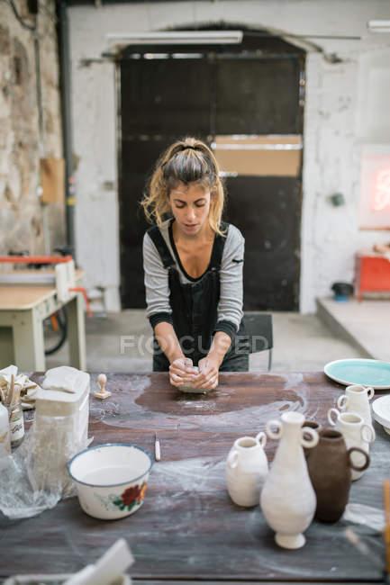 Вид женщины-гончара, замесившей глину на столе в мастерской — стоковое фото