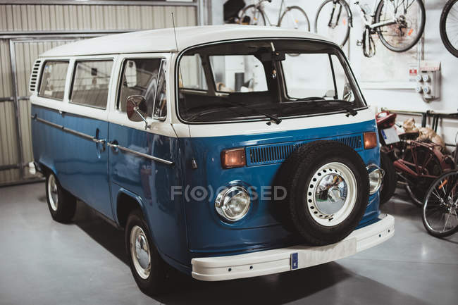 Shining retro van of blue and white color parked in garage. — Stock Photo