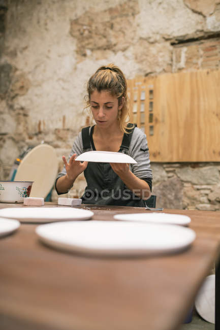 Concentrated female potter in apron sitting at table and creating plates from white clay. — Stock Photo