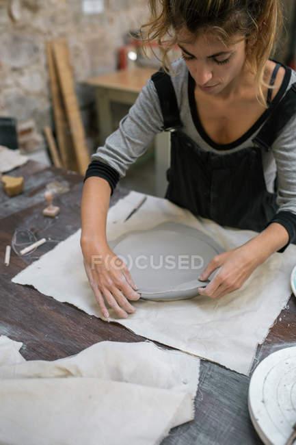 Retrato de oleiro trabalhando com argila na área de trabalho em oficina — Fotografia de Stock