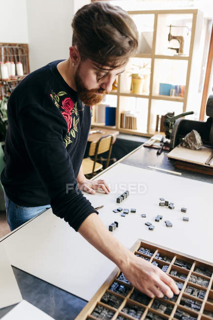 Рабочий, раскладывающий печатные письма в коробке на столе — стоковое фото