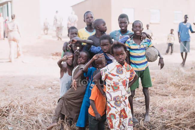 Goree, senegal- 6. Dezember 2017: Gruppe afrikanischer Kinder posiert gemeinsam gestikulierend mit V-Zeichen vor der Kamera auf der armen Straße. — Stockfoto