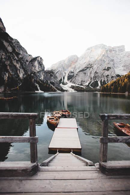 Petit quai et bateaux amarrés sur le lac près de majestueuse montagne enneigée . — Photo de stock
