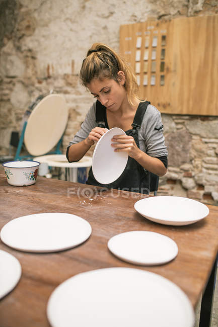 Concentrated woman in apron sitting at table and forming plates from white clay. — Stock Photo