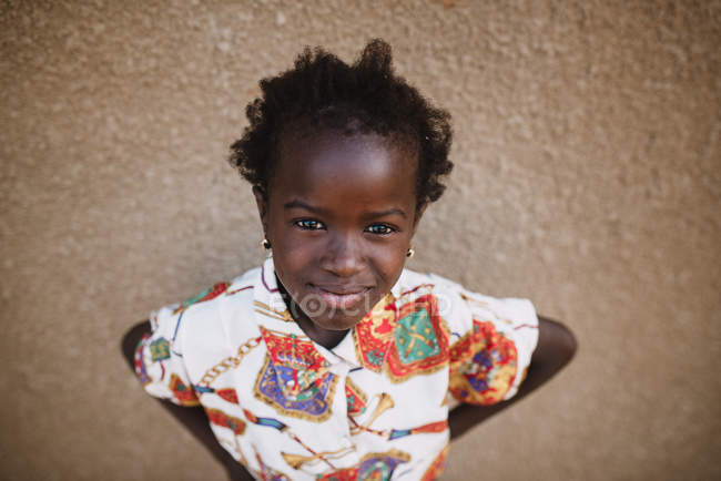 Goree, Senegal- December 6, 2017: Portrait of adorable girl in stylish bright dress looking confidently at camera. — Stock Photo