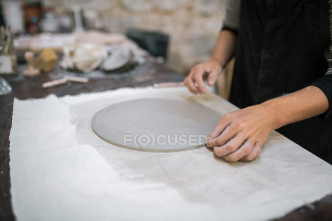 Crop female artisan working with circle of clay on table in pottery studio — Stock Photo