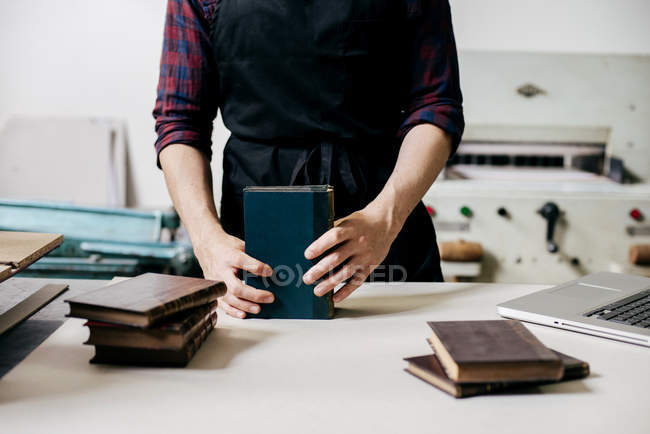 Mid section of man in apron arranging and creating leather notebooks. — Stock Photo