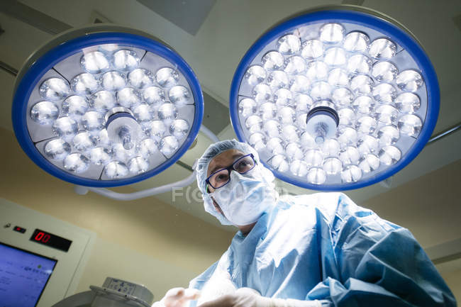 Bottom view of surgeon in uniform standing under bright lamps in operating room and looking away. — Stock Photo
