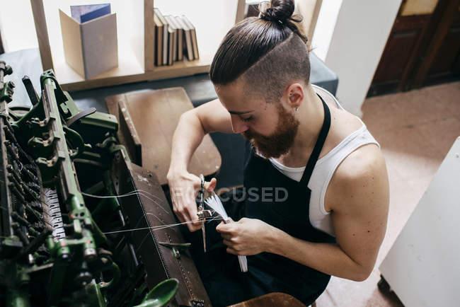Высокий угол обзора рабочих переплетных листов бумаги в мастерской — стоковое фото