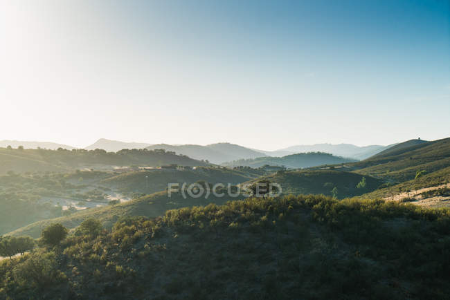 Scenic landscape of sunlit misty mountains valley — Stock Photo