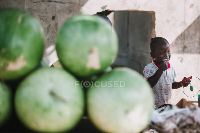 Goree, Senegal- 6 de diciembre de 2017: Montón de cocos verdes sobre una niña comiendo cocos en el mercado . - foto de stock