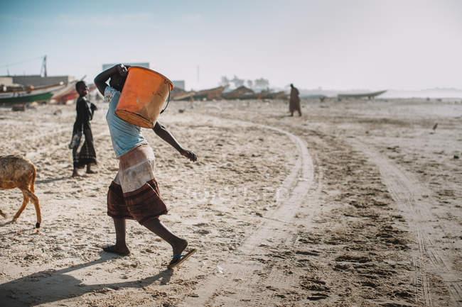 Yoff, Senegal - 6. Dezember 2017: Seitenansicht der Frau, die trägt orange Korb am Meer im afrikanischen Dorf. — Stockfoto