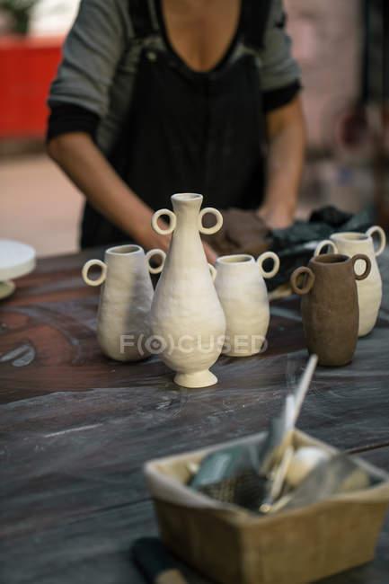 Panelas de barro artesanais na mesa de madeira na oficina de cerâmica — Fotografia de Stock