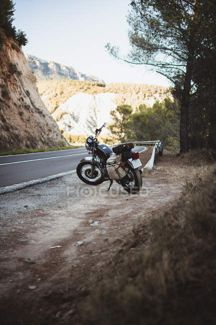 Motorcycle with travel bags parked on roadside. — Stock Photo