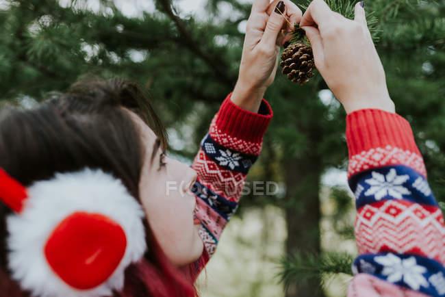 Sur l'épaule vue de fille en fourrure oreilles de Noël décoration conifères avec des cônes — Photo de stock