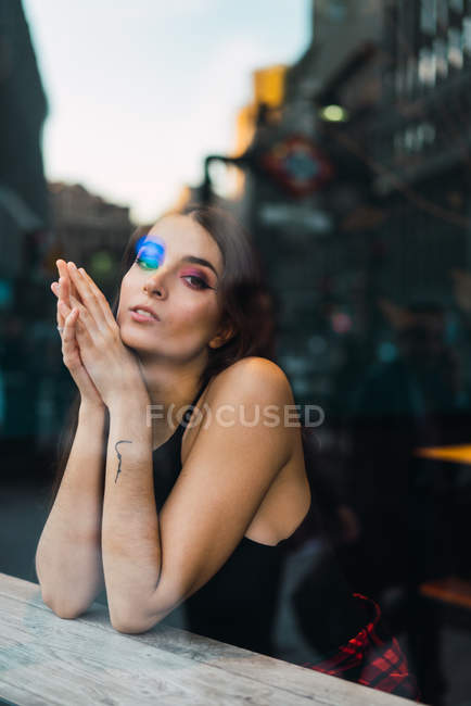Dreaming brunette girl in cafe looking through window at camera — Stock Photo