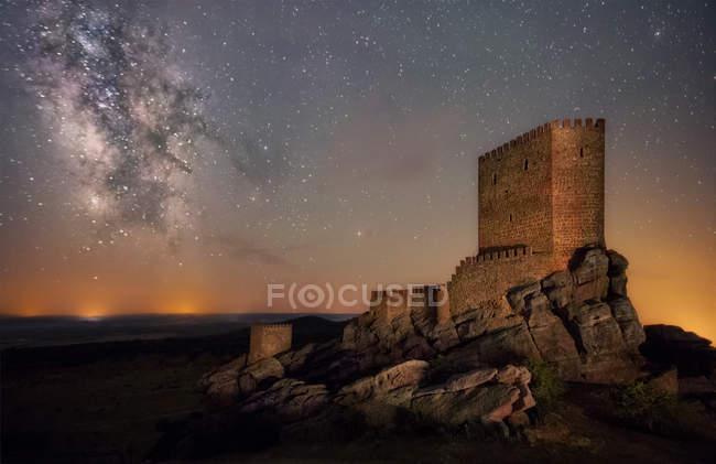 Зовнішній вигляд башти замку на пагорбі над сутінки небо — стокове фото