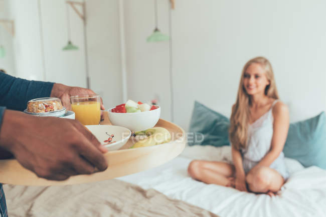 Crop male hands holding tray with breakfast in front of young blonde sitting in bed — Stock Photo