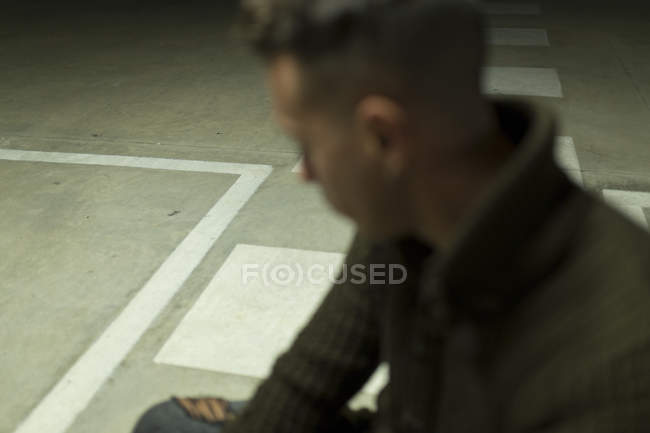 Side view of man sitting on concrete ground — Stock Photo
