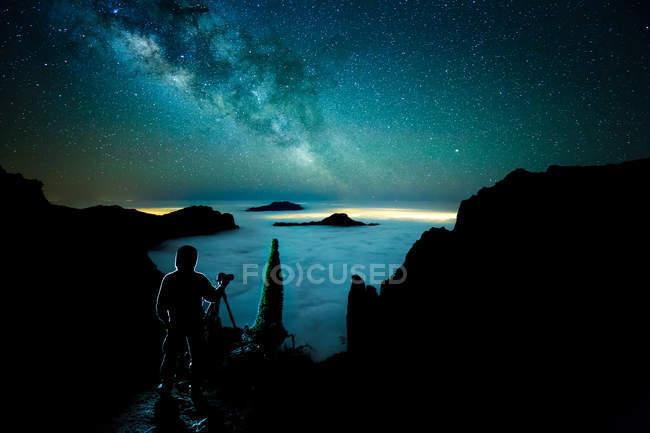 Силует особи, що приймають знімки морський пейзаж і ясно зоряного неба. — стокове фото