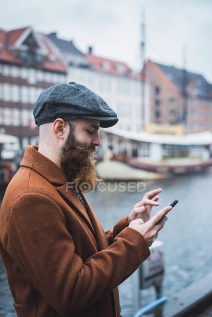 Vista lateral del hombre barbudo navegando teléfono inteligente en el río en la ciudad - foto de stock