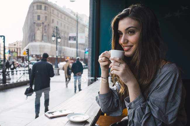 Portrait of smiling girl drinking coffee at city cafe — Stock Photo