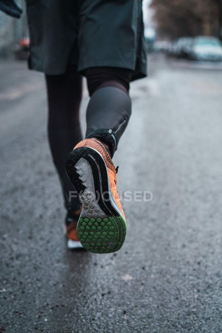 Low section of jogger in warm sportswear walking on street. — Stock Photo