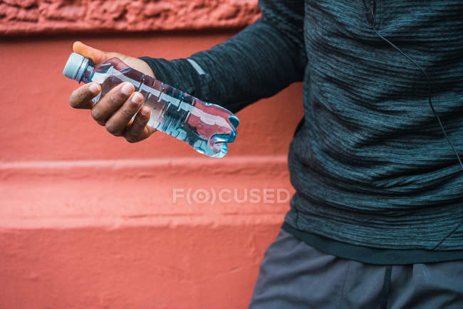 Crop male hand with bottle of water. — Stock Photo
