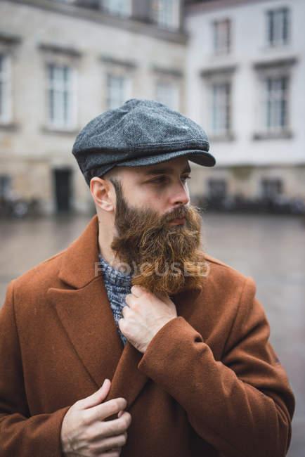 Портрет бородатого человека в пальто и кепке, позирующего на улице — стоковое фото