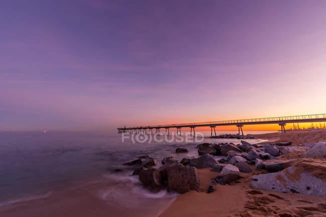 Coucher de soleil violet scénique sur un rivage avec jetée longue — Photo de stock