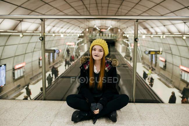 Portrait de jolie femme au Bonnet jaune assis sur le sol au passage du métro et regardant la caméra — Photo de stock