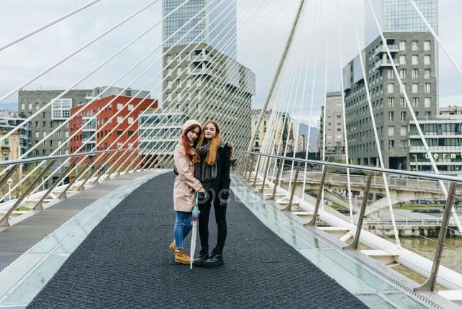 Two girls hugging and posing on bridge — Stock Photo