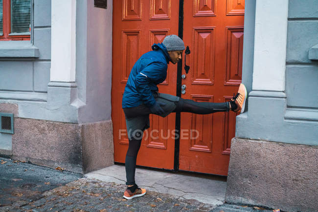 Side view of jogger man leaning on wall with leg and warming up and stretching muscles — Stock Photo
