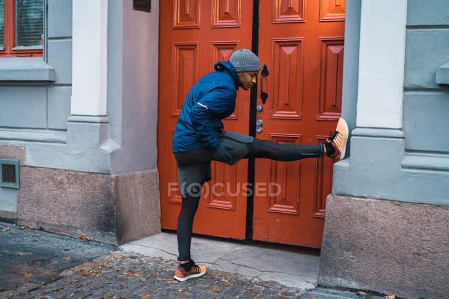 Seitenansicht der Jogger Mann stützte sich auf Wand mit Bein und Aufwärmen und Dehnen der Muskeln — Stockfoto
