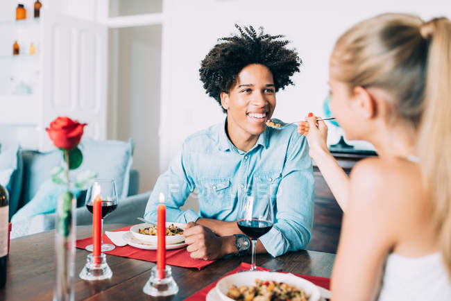 Portrait of smiling interracial couple having romantic dinner on valentines day at hom — Stock Photo