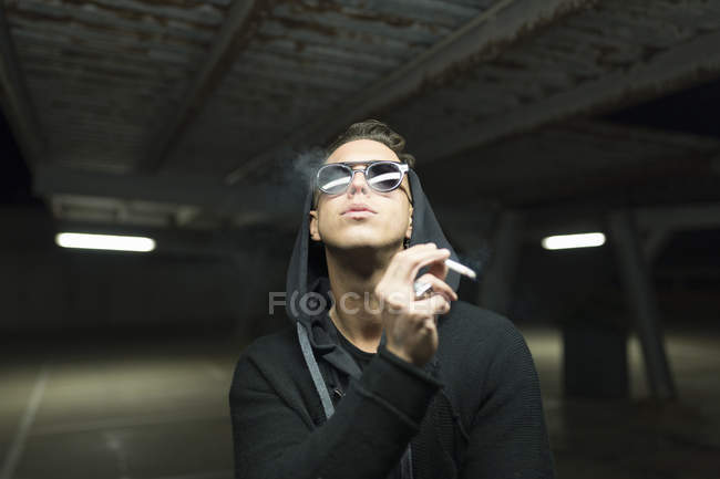 Portrait of trendy man in sunglasses and hoodie smoking cigarette at parking — Stock Photo