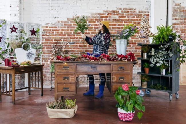 Portrait of woman arranging flowers at table in floral atelier — Stock Photo