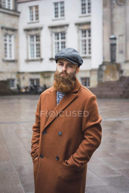 Ritratto di uomo barbuto in posa in cappotto vintage e cappello in posa in città — Foto stock