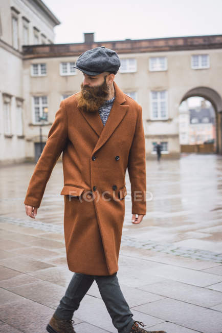 Portrait bearded man walking in city and looking over shoulder away — Stock Photo