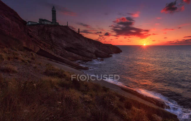 Scenic view to lighthouse on ocean shore in sunset light at seaside. — Stock Photo