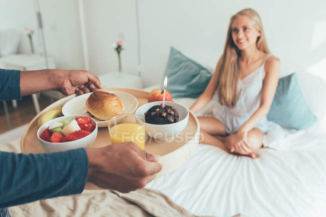 Crop male hands holding tray with birthday breakfast in front of young blonde sitting in bed — Stock Photo
