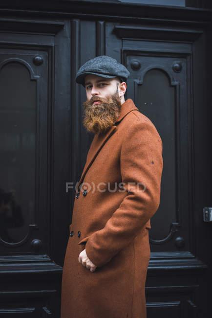Портрет стильного бородатого мужчины, позирующего над черной дверью — стоковое фото